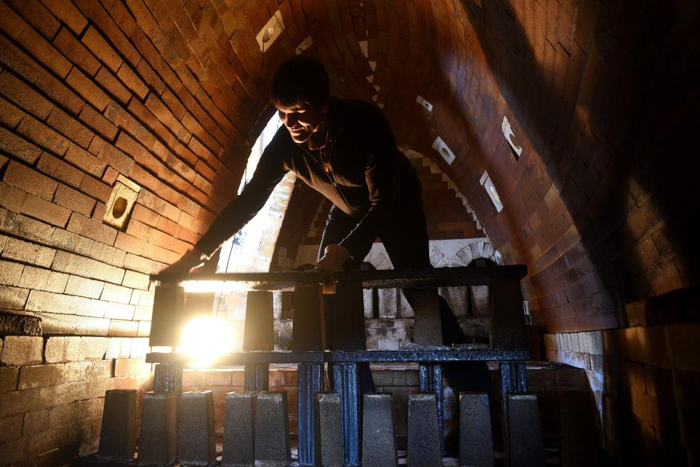 Nathan Webb dismantles shelving inside the wood-fired kiln at Two Potters studio in Bethel, Vt. Wednesday, March 11, 2015. Webb and his wife Becca fire the kiln twice a year for between four and five days each time. (Valley News - James M. Patterson) <p><i>Copyright © Valley News. May not be reprinted or used online without permission. Send requests to permission@vnews.com.</i></p> - James M. Patterson | Valley News