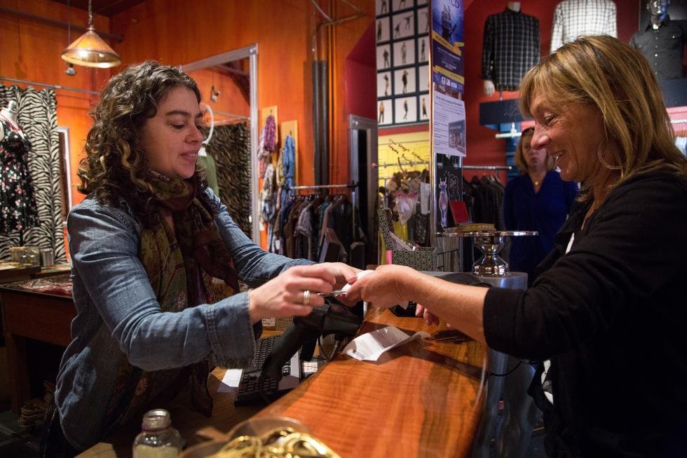 Ann Laflamme, of Littleton, N.H., right, takes her receipt from owner Kim Souza after buying a dress at Revolution in White River Junction, Vt., on Saturday, April 11, 2015. Souza opened the small vintage clothing boutique in 2002. The shop now features clothing and jewelry from local designers in addition to its vintage and consignment pieces. (Valley News - Sarah Shaw) <p><i>Copyright © Valley News. May not be reprinted or used online without permission. Send requests to permission@vnews.com.</i></p> - Sarah Shaw   Valley News
