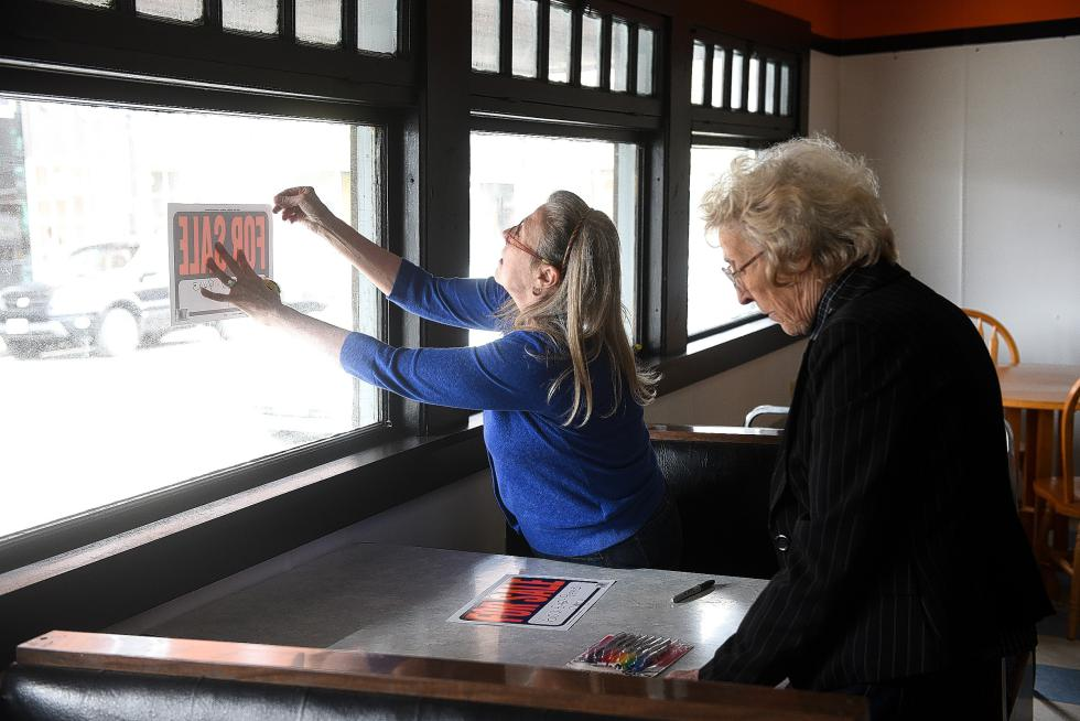After reminiscing about the Polka Dot Restaurant's heyday, owner Mary Shatney, right, and her daughter Sherry Greene, left, who worked for her mother as a waitress while growing up, prepare for sale signs to tape in the windows Thursday, April 30, 2015. The building, where Shatney first worked in 1959, sits on land owned by the Canadian National Railway.   (Valley News - James M. Patterson) <p><i>Copyright © Valley News. May not be reprinted or used online without permission. Send requests to permission@vnews.com.</i></p> - James M. Patterson | Valley News