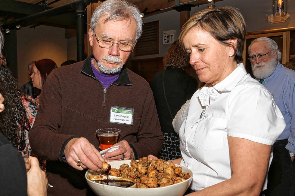 Larry Ference, of Farms for City Kids in Reading, Vt., samples the food served by LIsa Weiss of Simon Pearce at the Chamber-to-Chamber mixer on Feb. 10 at Simon Pearce in Quechee, hosted by the Woodstock Area Chamber of Commerce and the Hartford Area Chamber of Commerce. (Gloria Towne photograph/allaroundtowne.com) - gloria towne |