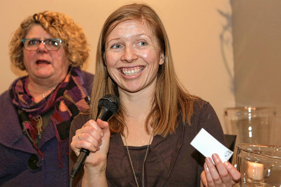Simon Pearce marketing director Meghan Mahoney pulls a business card during the raffle at the Chamber-to-Chamber mixer on Feb. 10 at Simon Pearce in Quechee, hosted by the Woodstock Area Chamber of Commerce and the Hartford Area Chamber of Commerce. Beth Finlayson, director of the Woodstock Chamber, is at left.  (Gloria Towne photograph/allaroundtowne.com) - Gloria Towne |