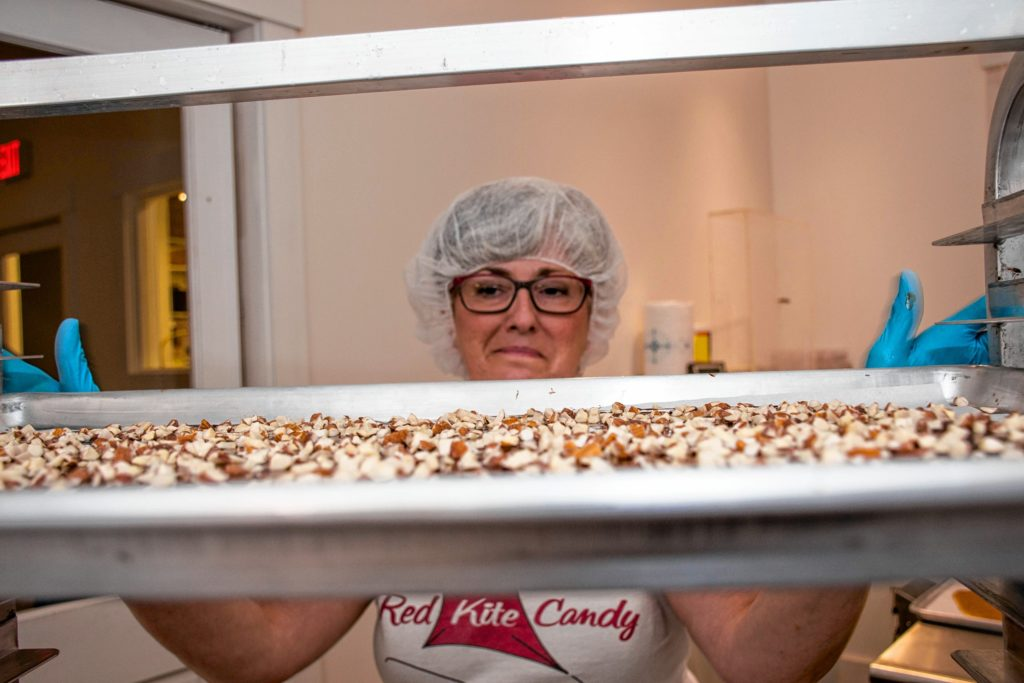 Red Kite Candy Co.'s Elaine McCabe places chocolate-coated toffee on racks to harden. After cooling for about an hour, the toffee will be flipped and the second side will be coated with Belgian chocolate and roasted organic almonds. Nancy Nutile-McMenemy photograph.