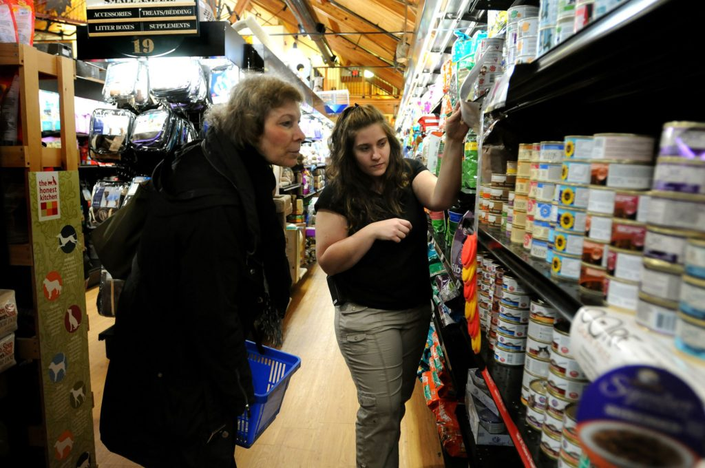 At West Lebanon Feed and Supply on Oct. 31, 2013, in West Lebanon, N.H., employee Melissa Gumm helps customer Linda Galvan, of East Thetford, Vt., pick out food out for her cats. (Valley News - Jennifer Hauck) Copyright Valley News. May not be reprinted or used online without permission. Send requests to permission@vnews.com.