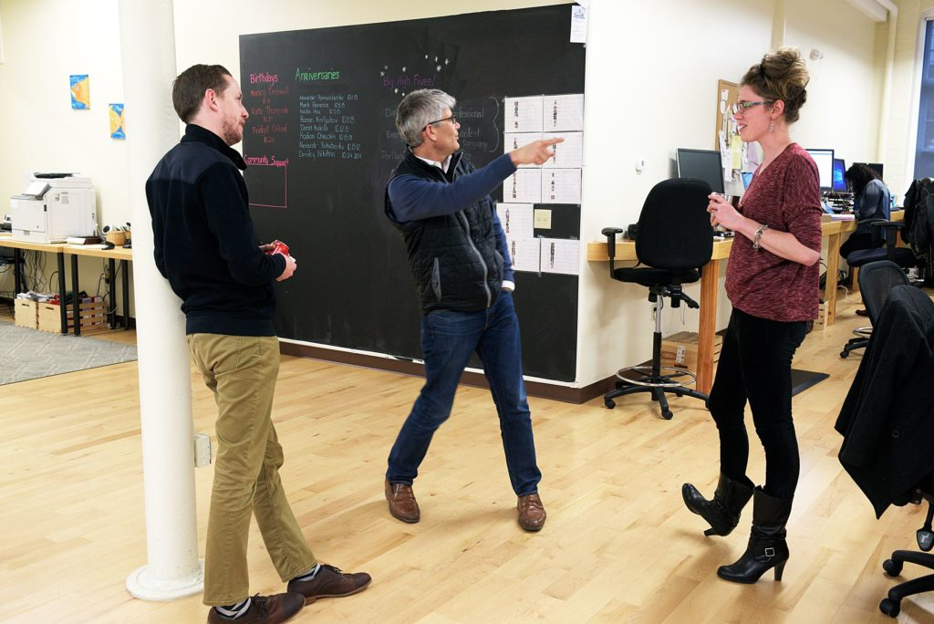 Director of Partnerships Tom Scully, left, CEO Chris Forman, middle, and account manager Alison Bowen, right, stop to converse as their paths cross in the office of Appcast in Lebanon, N.H., Thursday, October 27, 2016. The company serves as a digital medium between large employers and publishers of job ads. (Valley News - James M. Patterson) Copyright Valley News. May not be reprinted or used online without permission. Send requests to permission@vnews.com.