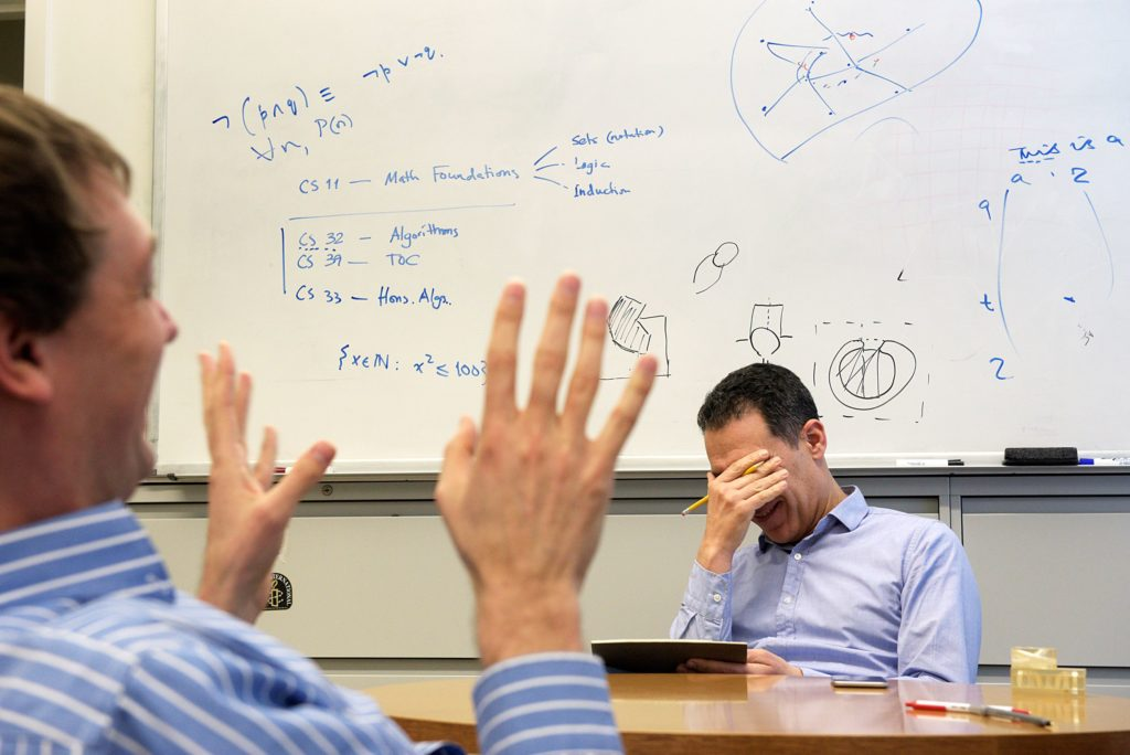 Hany Farid, of Norwich, laughs with associate professor of computer science Devin Balkcom while planning a course for Tuck business school students in Hanover, N.H., Wednesday, February 15, 2017. (Valley News - James M. Patterson) Copyright Valley News. May not be reprinted or used online without permission. Send requests to permission@vnews.com.