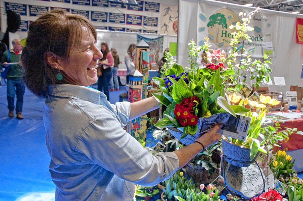 ( A COLORFUL DISPLAY Sylvia Provost, owner of Henderson's Tree & Garden Services in White River Junction, shows off some spring flowers at the 2015 Flavors of the Valley event.