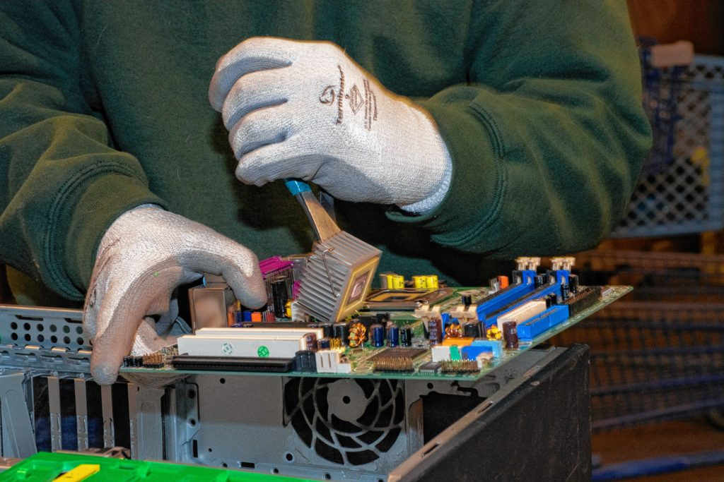 Ken picks apart a motherboard. Nancy Nutile-McMenemy photograph