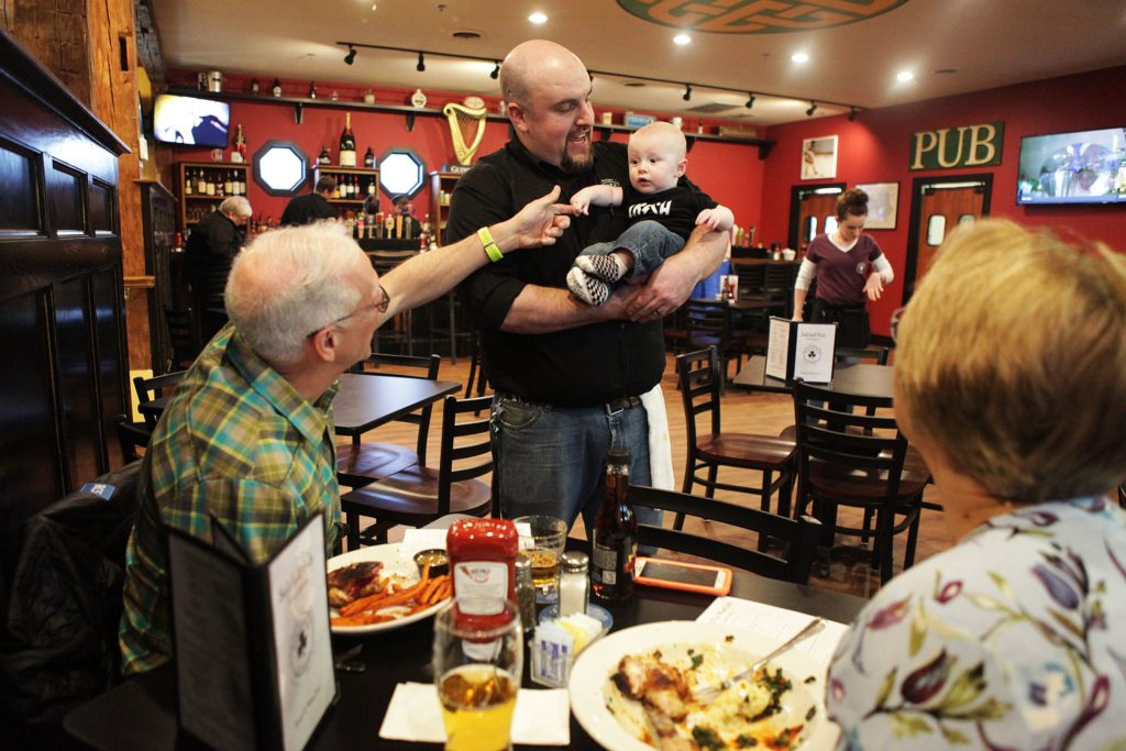 : PRE-PARTYEnfield resident Dave Albert, left, greets 6-month-old Benjamin McGary, held by his father, Josh McGary, the regional manager of Salt hill Pub, at the pre-opening party for the pub's newest location in West Lebanon.