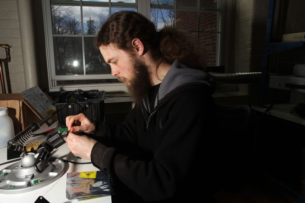 Nick Conquest, an electrical engineer and technician at Simbex, tests old prototypes of the company's head impact technology measuring system on Thursday, April 13, 2017, in Lebanon, N.H. (Valley News - Jovelle Tamayo) Copyright Valley News. May not be reprinted or used online without permission. Send requests to permission@vnews.com.