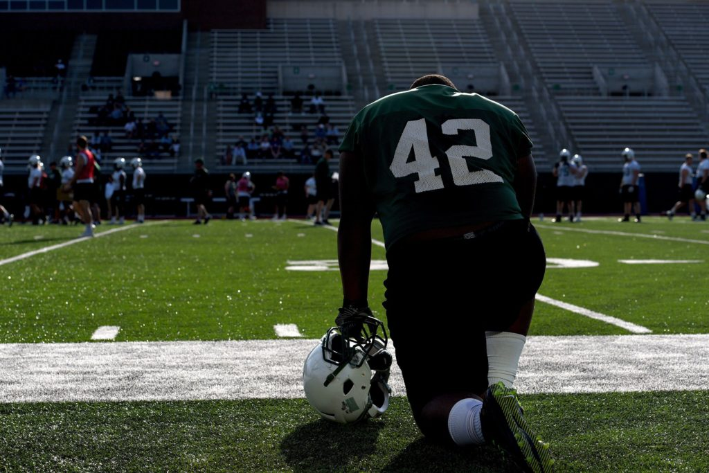 Dartmouth football player Davaron Stockman watches practice on April 28, 2017. Some players have sensors implanted in their helmets.  (Valley News - Jennifer Hauck) Copyright Valley News. May not be reprinted or used online without permission. Send requests to permission@vnews.com.