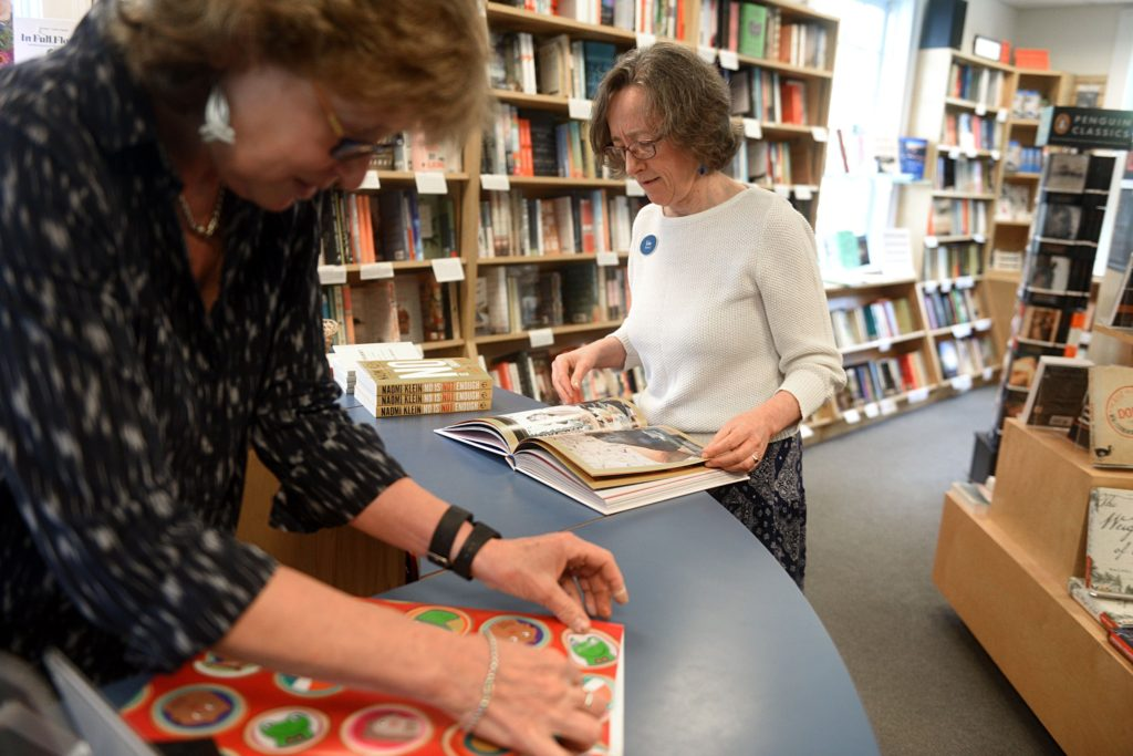 Carin Pratt, left, wraps a gift for a customer as Liza Bernard pages through a book at the Norwich Bookstore on June 13, 2017, in Norwich, Vt. (Valley News - Jennifer Hauck) Copyright Valley News. May not be reprinted or used online without permission. Send requests to permission@vnews.com.