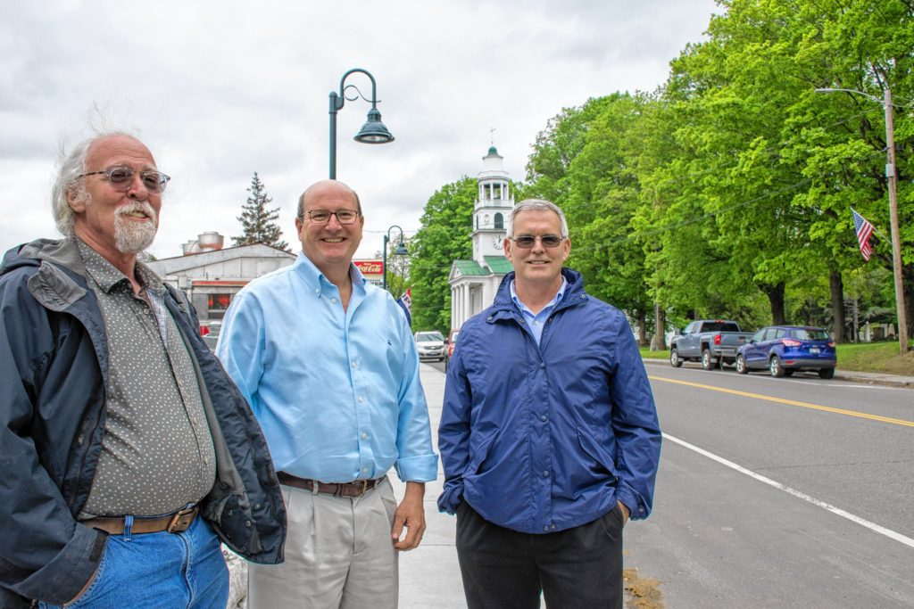 Bob Haight (left), Tom Marsh (center) and John Tansey (right) of Distinctly Windsor stand on one of the town's recent infrastructure projects along Main Street, a new sidewalk and railing. Nancy Nutile-McMenemy photograph.