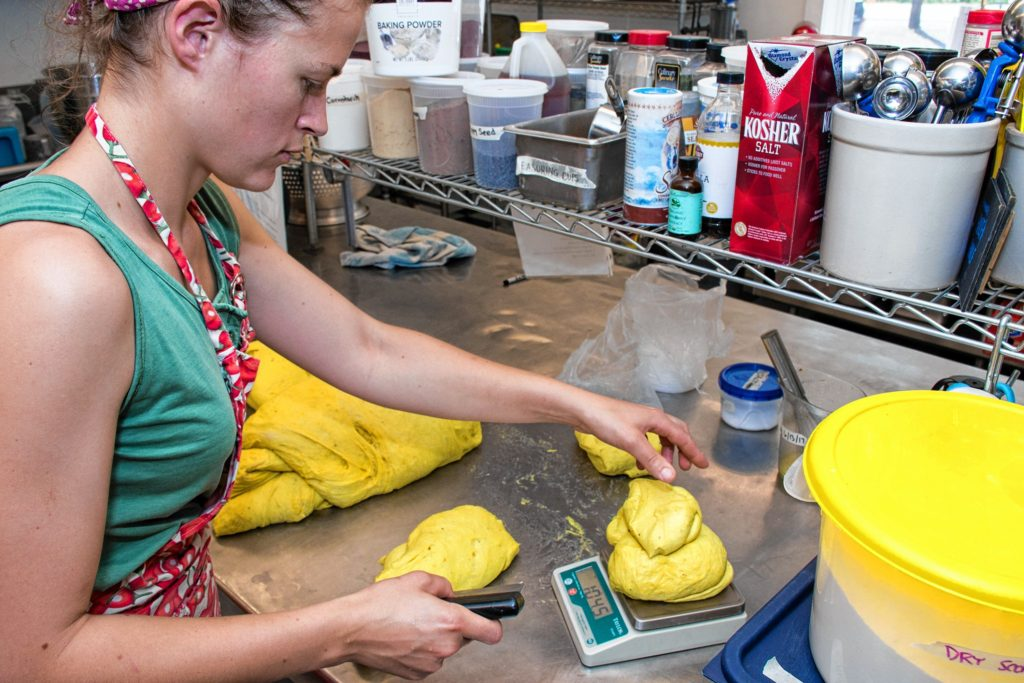 Edgewater Farm kitchen manager Emily Malnati carefully weighs out a pound of dough for honey curry bread in Plainfield, N.H. Nancy Nutile-McMenemy photograph.
