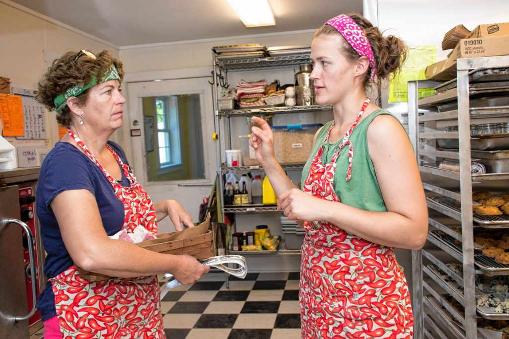 Shannon Buskey, left, listens to Emily Malnati list off the new labels that need to be made at Edgewater Farm in Plainfield, N.H. Nancy Nutile-McMenemy photograph.
