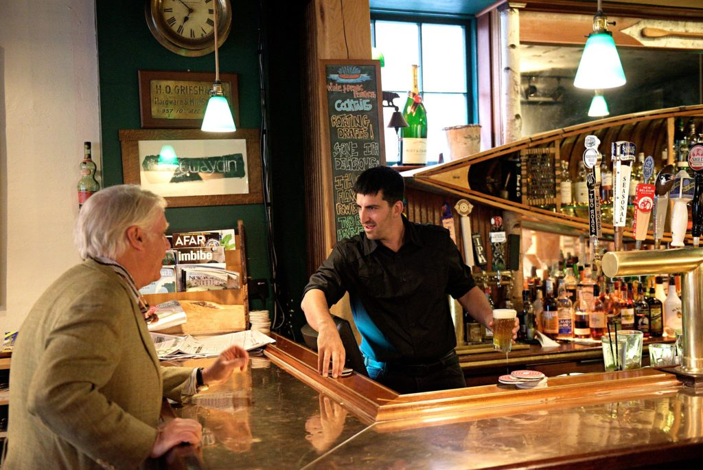 After over 13 years at the helm of the Canoe Club in Hanover, N.H., John Chapin, left, has sold the restaurant and bar to to bartender Daniel Levitt, right, who has been on staff since the establishment opened in 2003. Chapin talks with Levitt between at the bar in Hanover, N.H. Friday, July 14,2 017. (Valley News - James M. Patterson) Copyright Valley News. May not be reprinted or used online without permission. Send requests to permission@vnews.com.