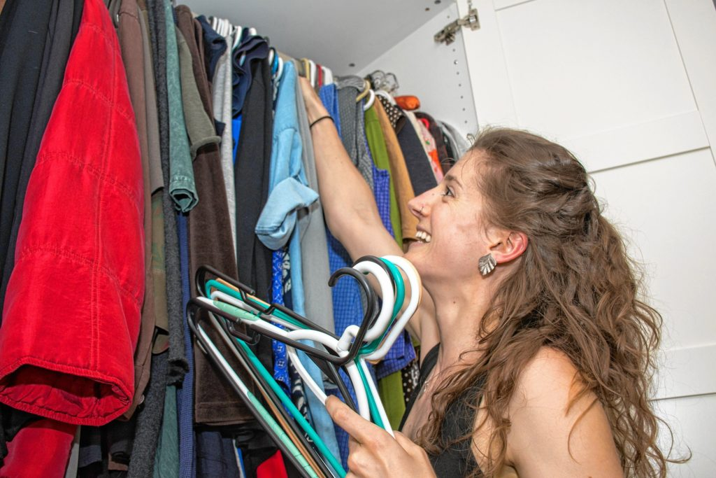 Loomis meets with clients and makes suggestions on how to organize your closets. Here she is switching out the winter items for summer. She will work with her client to sort items for donation, thrown away and keep. Nancy Nutile-McMenemy photograph.