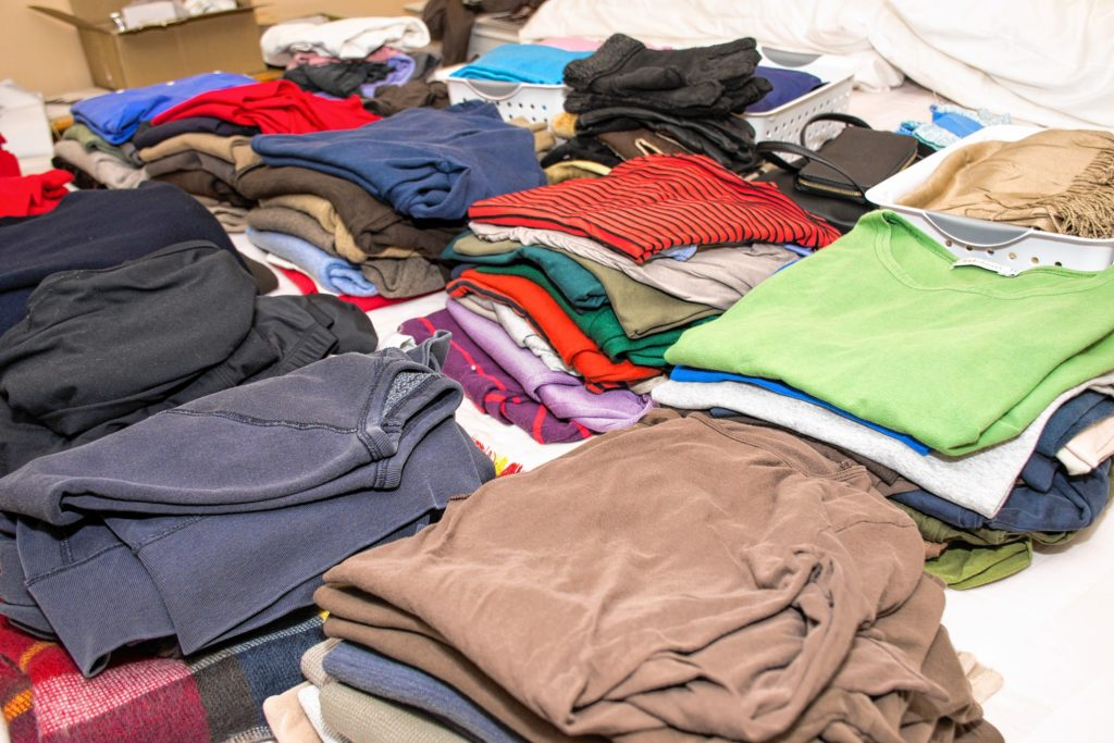 Piles of winter clothes wait for the client and Loomis to sort through. Nancy Nutile-McMenemy photograph.