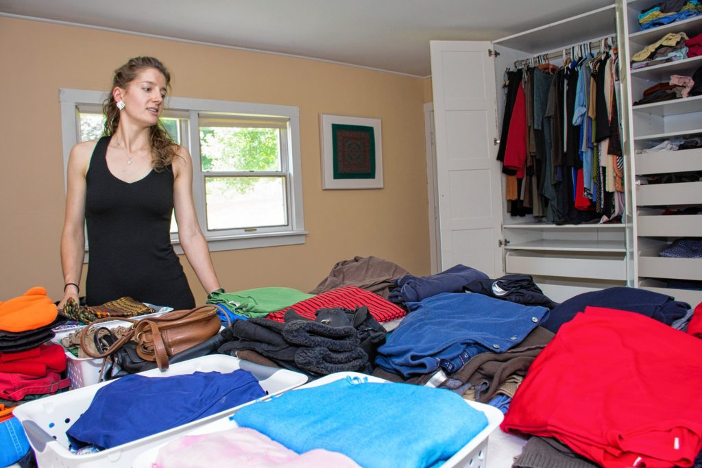 Loomis organizes the piles before calling the client into the bedroom to discuss what to keep and what not to keep. Nancy Nutile-McMenemy photograph.
