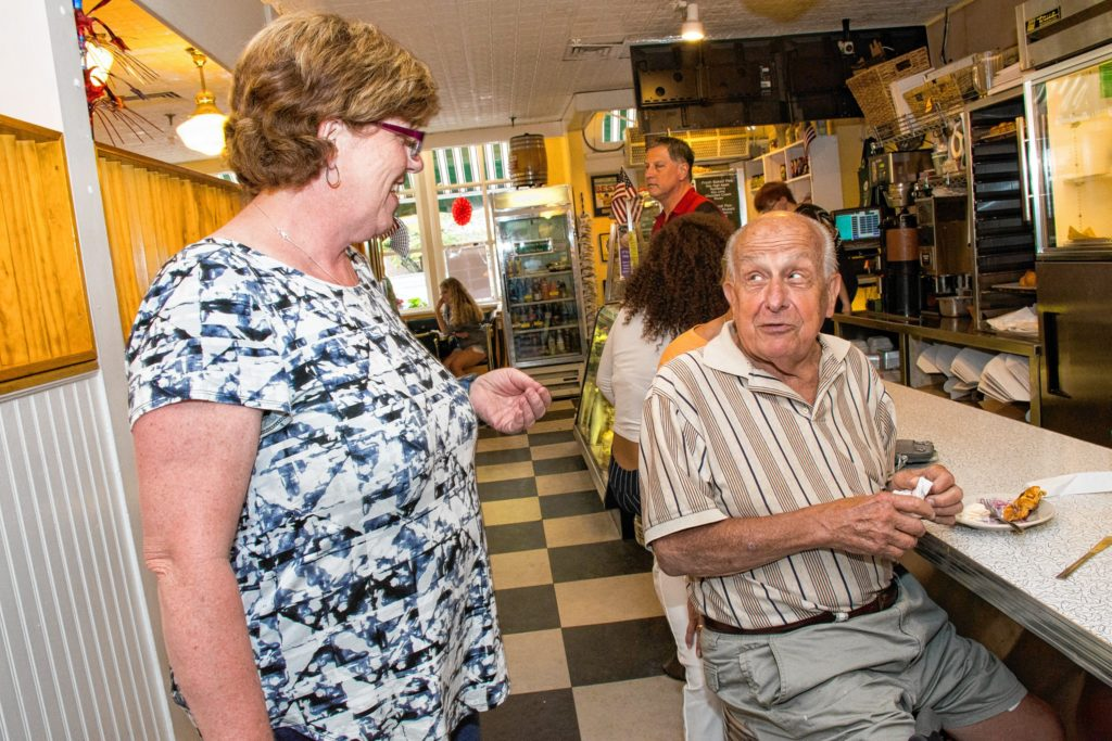 Pattie Fried (left)stops to listens to Lawrence Ferlan (right) from Pittsburgh, PA compliment her on the peach blueberry pie a la mode that he just finished. Ferlan has a second home place in New London and stopped into Lou's for a piece of pie. Nancy Nutile-McMenemy photograph.