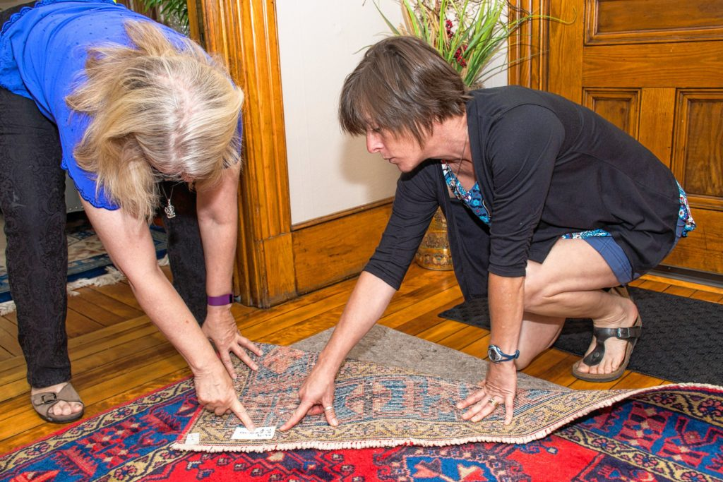Eileen O'Connor, of West Lebanon, NH (left) has an extensive collection of rugs that she rotates seasonal throughout her home. Sarah Dole of Easy Peasy Organizing (right) developed a labeling system to match the rugs with the correct padding so Eileen could save time when swapping the rugs out. Nancy Nutile-McMenemy photograph.