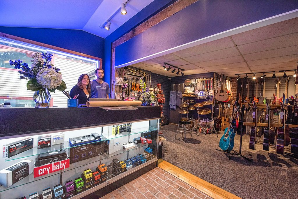 Barb McKelvy, left, and her business partner, Tyler Geno, have reopened Blue Mountain Guitar in an alcove of shops on Main Street in New London, directly across from Colby-Sawyer College. (Courtesy photograph)