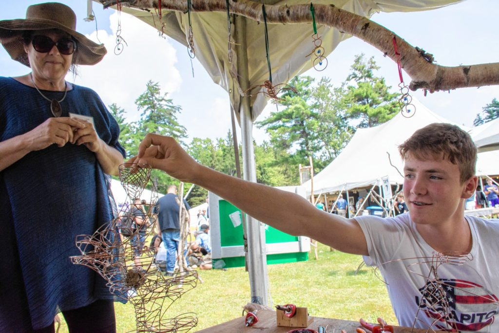 Miriam Carter, left, executive director of the League of New Hampshire Craftsmen, makes a stop at the Next Generation Tent to visit with Leo Reinbard-Adler, right, a young artist from Switzerland who creates marble tracks. (Nancy Nutile-McMenemy photograph)