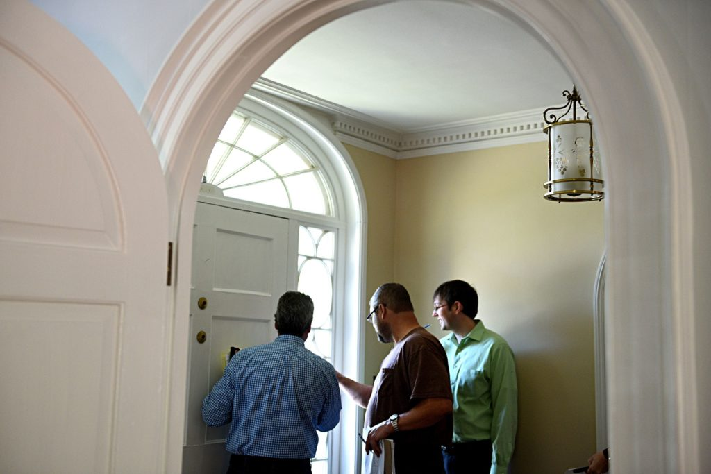 Todd Thompson vice president and project manger of Trumbull-Nelson, left, Dave Stanley superintendent at Trumbull-Nelson and Ben Van Vliet, executive director at the Upper Valley Music Center look at a crack in the glass surrounding a door in Lebanon, N.H. on Sept. 11, 2017.  (Valley News - Jennifer Hauck) Copyright Valley News. May not be reprinted or used online without permission. Send requests to permission@vnews.com.