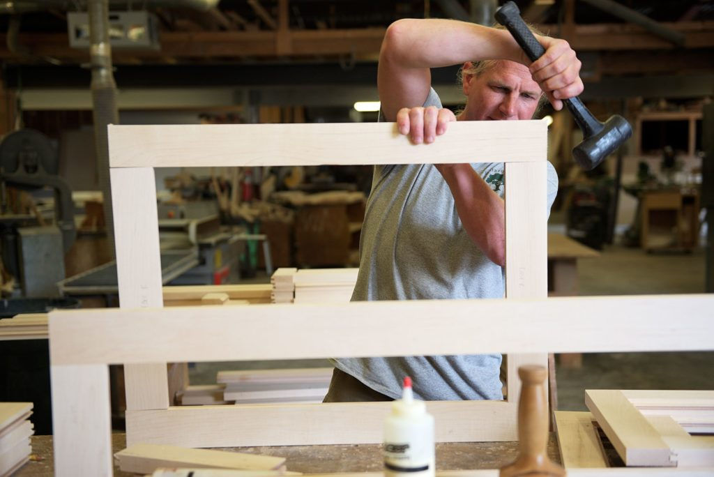 Cabinet maker Andy Mulligan fits together the frame of a cabinet door for a residential customer in the carpentry shop of Trumbull-Nelson Construction Company in Hanover, N.H., where he has worked a total of ten years, Thursday, September 15, 2017. Trumbull-Nelson is celebrating 100 years since its founding in 1917. (Valley News - James M. Patterson) Copyright Valley News. May not be reprinted or used online without permission. Send requests to permission@vnews.com.