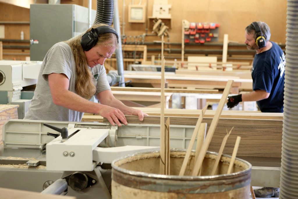 Andy Mulligan, left, and John Bulk, right, plane boards in the carpentry shop at Trumbull-Nelson Construction Company in Hanover, N.H., Thursday, September 15, 2017. The company is celebrating 100 years since its founding in 1917.(Valley News - James M. Patterson) Copyright Valley News. May not be reprinted or used online without permission. Send requests to permission@vnews.com.