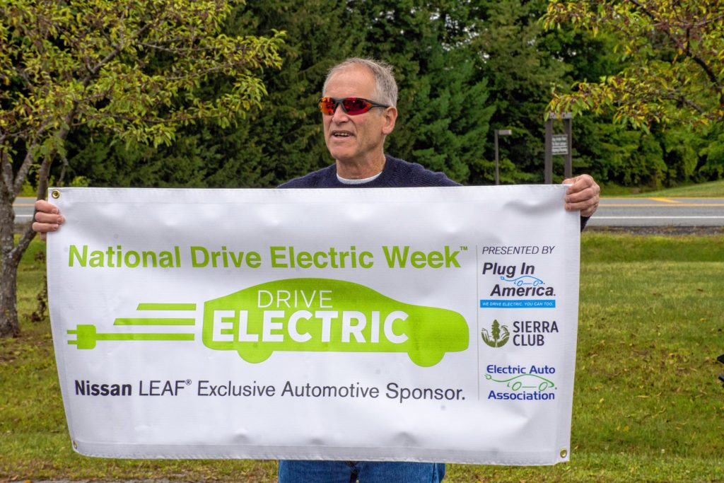 Jamie Hess, a member of the New London (N.H.) Energy Committee, holds one of the many banners that were on display at the second annual Upper Valley Electric Vehicle Expo on Sept. 9 at Dothan Brook School in Hartford, Vt. (Nancy Nutile-McMenemy photograph)
