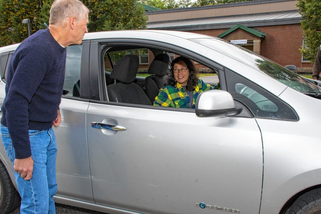 Jamie Hess, left, speaks with Mary Boyle, a member of the Cornish (N.H.) Energy Committee who was showing her electric Nissan Leaf at the Upper Valley Electric Vehicle Expo on Sept. 9 at Dothan Brook School in Hartford, Vt. (Nancy Nutile-McMenemy photograph)