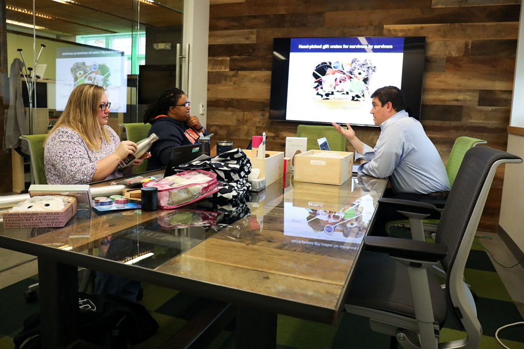 Jen Jones, left, and her wife Dia Draper, both of Hanover, N.H., talk with Jamie Coughlin, director at the DEN Innovation Center, during a meeting for Draper's business, Gift Crate, on Monday, Oct. 23, 2017, at the DEN Innovation Center in Hanover, N.H. Gift Crate, a care package business for cancer survivors, was started by Draper after she was treated for colon cancer. (Valley News - Charles Hatcher) Copyright Valley News. May not be reprinted or used online without permission. Send requests to permission@vnews.com