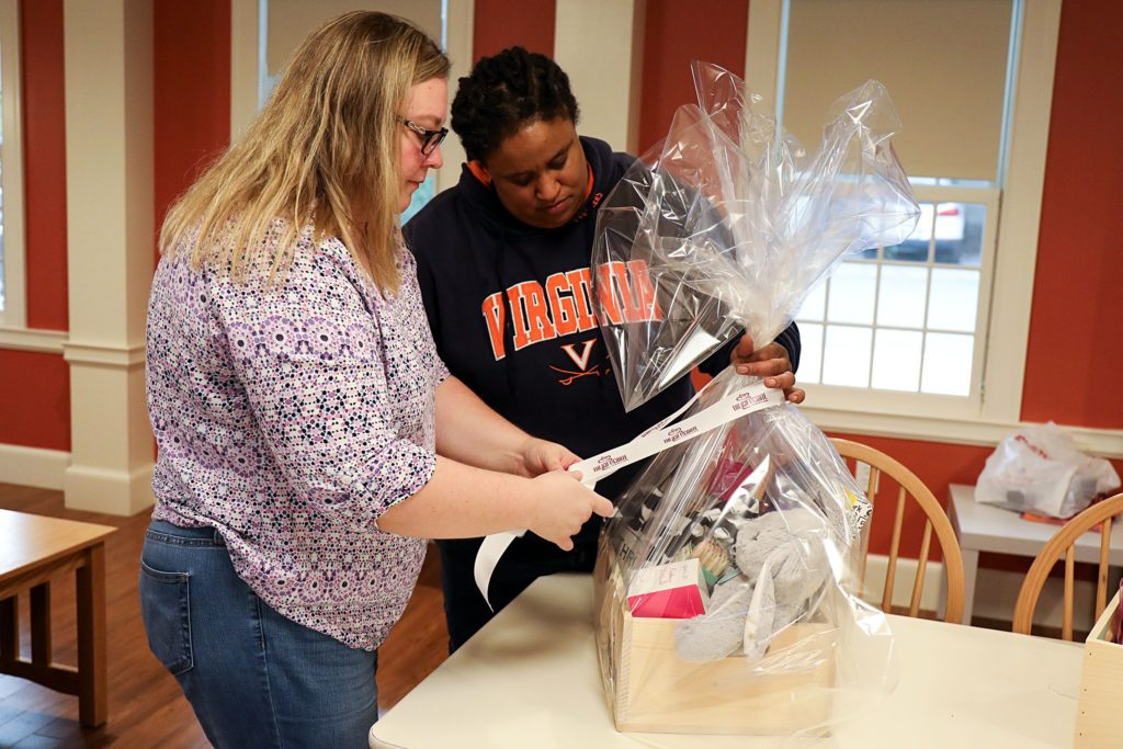 Jen Jones, left, of Hanover, N.H., ties a bow on a Gift Crate, with help from her wife, Dia Draper, also of Hanover, on Monday, Oct. 23, 2017, in the common area of the Triangle House on Dartmouth College campus in Hanover, N.H. The couple works on the business together sending care packages to cancer survivors. (Valley News - Charles Hatcher) Copyright Valley News. May not be reprinted or used online without permission. Send requests to permission@vnews.com