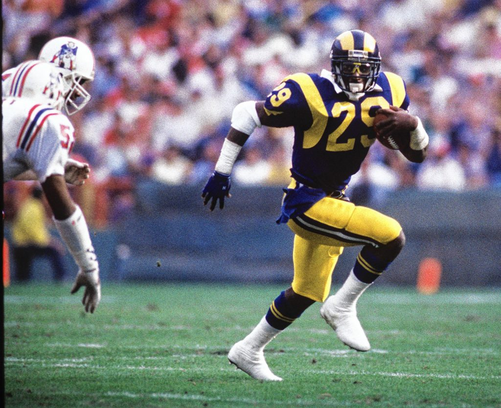 Eric Dickerson carries the ball against members of the New England Patriots defense in this file photo. (Christine Cotter/Los Angeles Times/TNS)