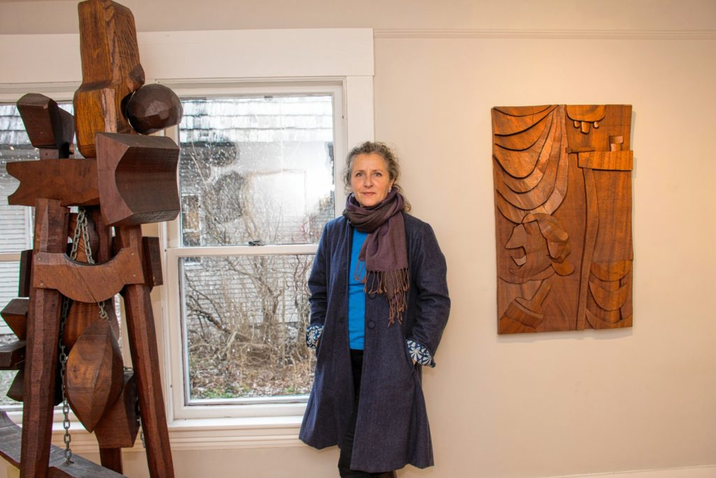 Anni Mackay poses between a couple of pieces created by Hugh Townley. Nancy Nutile-McMenemy photograph.