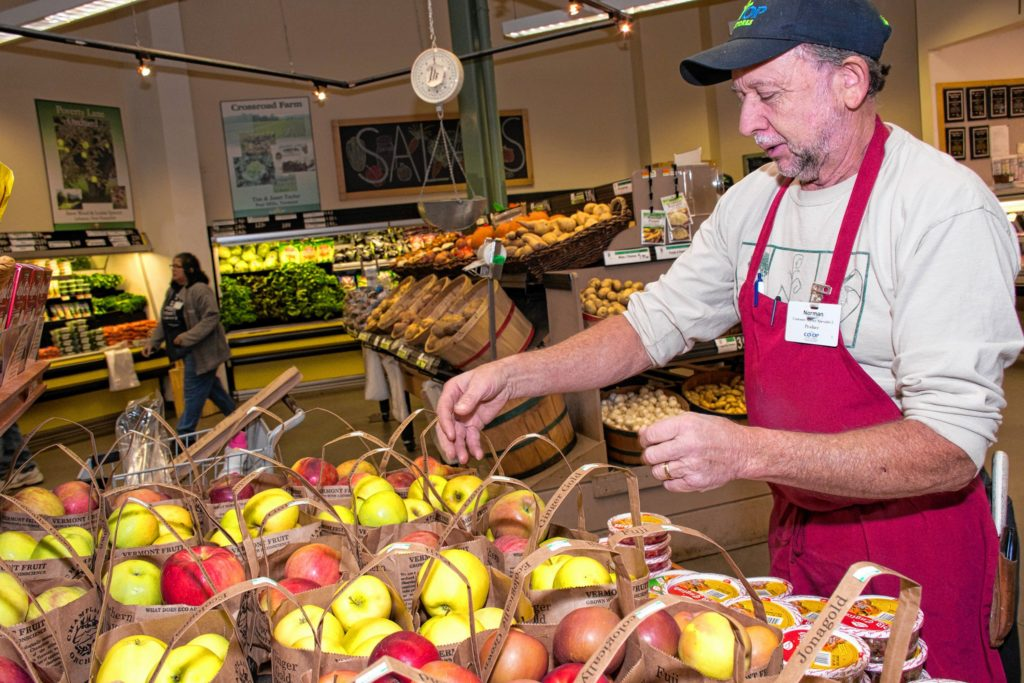 Norman Porter from White River Junction has been with the Co-Op for 10 years. He watches consumers and is there to answer questions about the fruits and vegetables the Co-Op carries. He even makes suggestions on packing to suppliers, like putting the names on apples on the handles so consumers can easily see what variety is in the bag. Nancy Nutile-McMenemy photograph.