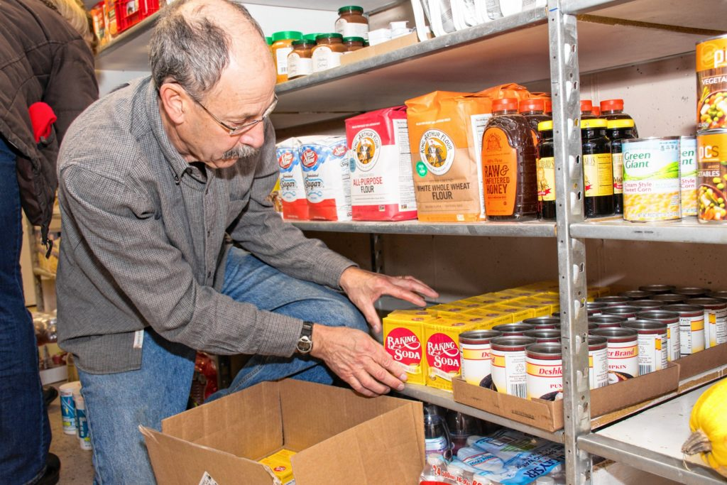 Robert Owens from Lebanon NH arranges some baking soda on the shelf. Nancy Nutile-McMenemy photograph.