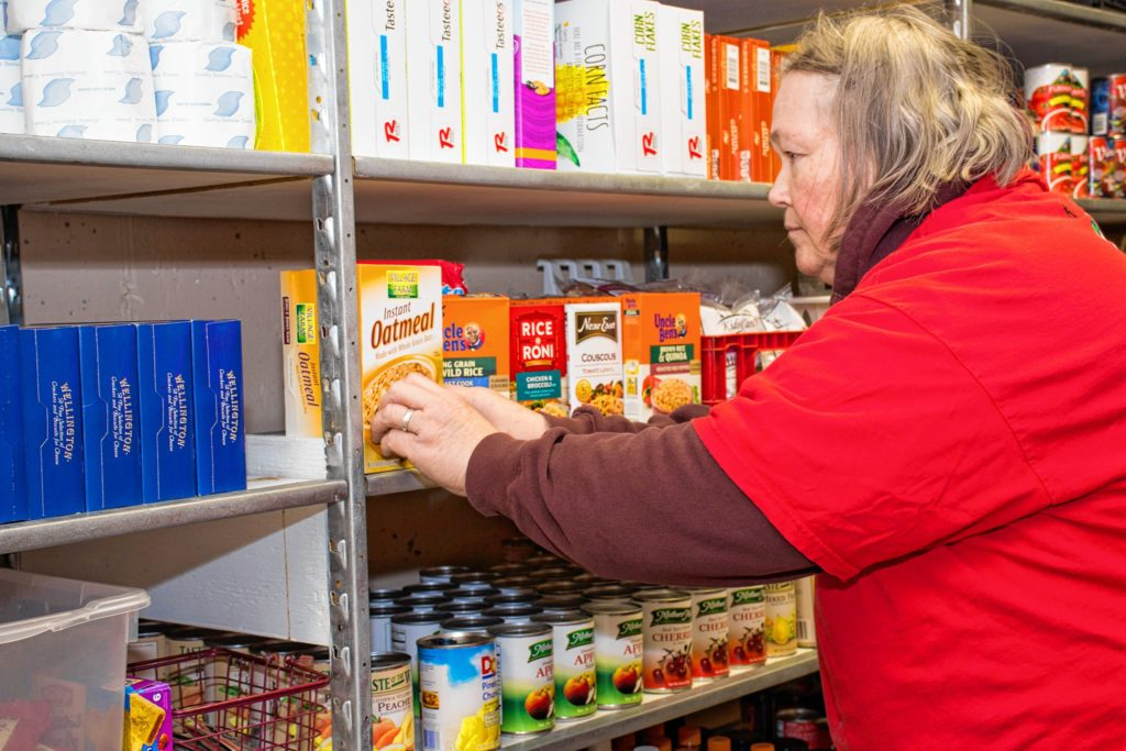 King Arthur Flour (KAF) employee and Wellspring Worship Center food shelf volunteer, Mary Tinkham basically runs the food shelf but also lends a hand stocking the shelves when needed. Nancy Nutile-McMenemy photograph.