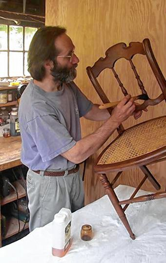 Gary Wood, owner of Gary R. Wood & Co., uses a special mop brush to apply finish to an antique chair in 2008. (Photo courtesy of Gary R. Wood & Co.)