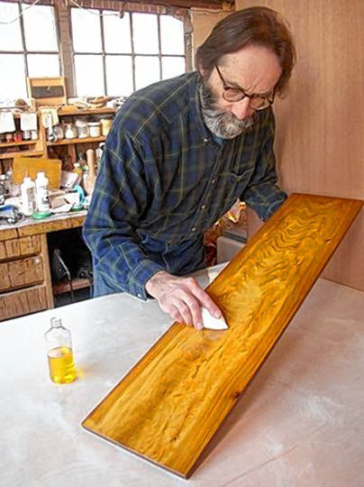 Gary R. Wood of Gary R. Wood & Co. French polishes a sample board for a finishing demonstration in 2013. (Photo courtesy of Gary R. Wood & Co.)