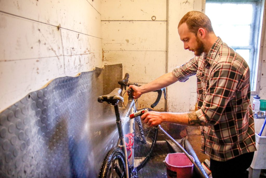 Robbie Boody, of Sharon, Vt., washes off a bike in Drummond Cycles in Enfield, N.H., on Wednesday, June 5, 2018. Each bike that comes into the shop for a tune up gets a standard washing treatment. (Valley News - August Frank) Copyright Valley News. May not be reprinted or used online without permission. Send requests to permission@vnews.com.
