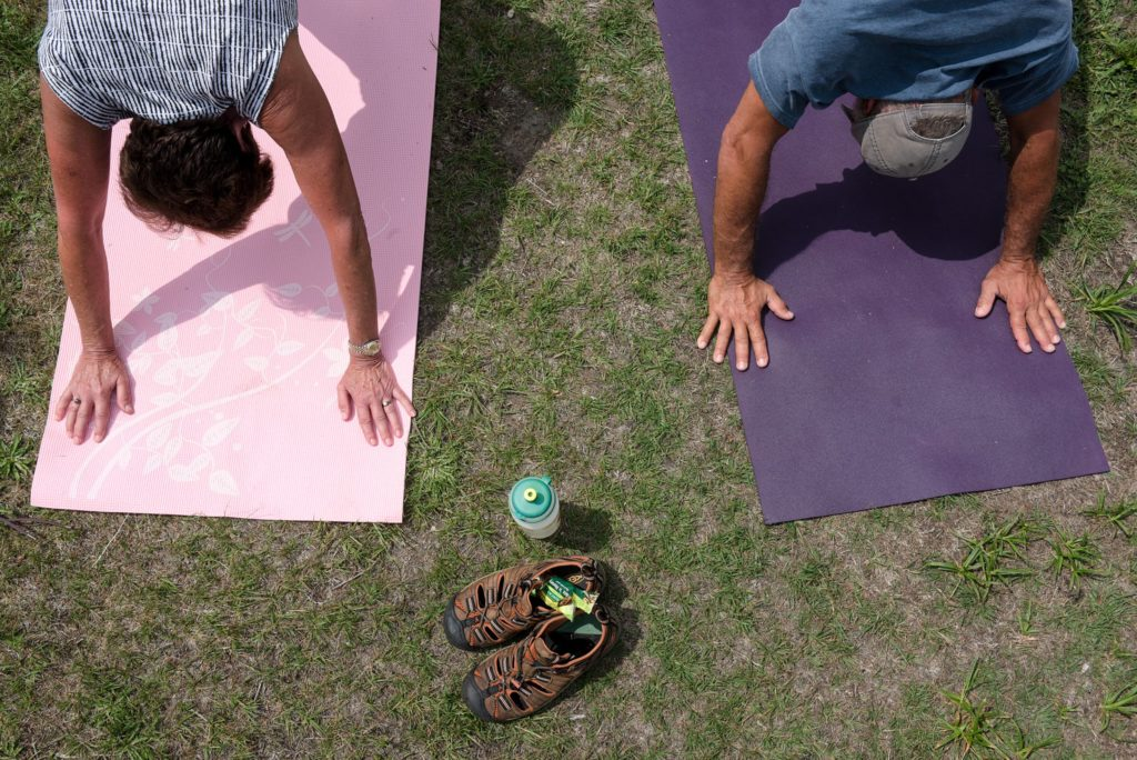 Linda Sacco, left, and Arthur Sacco, of Newbury, hold their downward dog position during yoga at the top of Mount Sunapee in Newbury, N.H., Wednesday, July 11, 2018. (Valley News - James M. Patterson) Copyright Valley News. May not be reprinted or used online without permission. Send requests to permission@vnews.com.