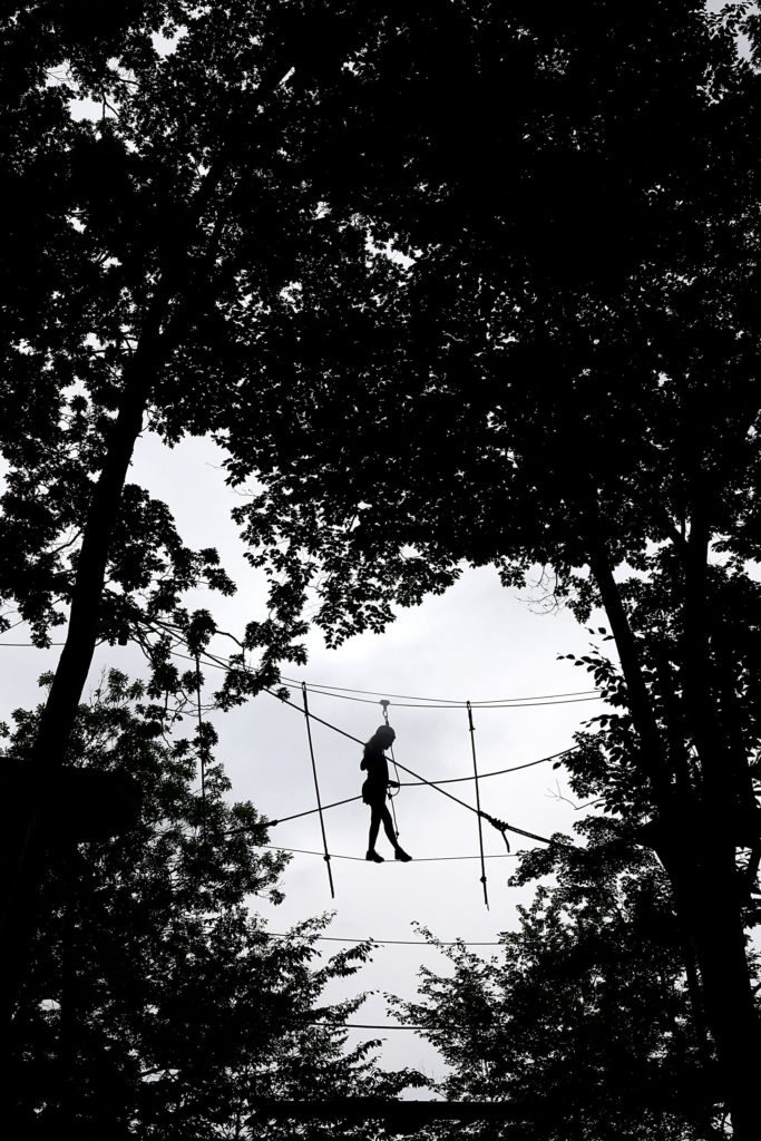 While buckled in with a harness, Molly Flaherty, 15, of Foxborough, Mass., watches her step as she negotiates a tightrope at  the Aerial Challenge Course at Mount Sunapee Resort's Adventure Park in Sunapee, N.H., on July 14, 2018. The resort has added several recreational activities, including the course, to become a year-round destination. (Valley News - Geoff Hansen) Copyright Valley News. May not be reprinted or used online without permission. Send requests to permission@vnews.com.