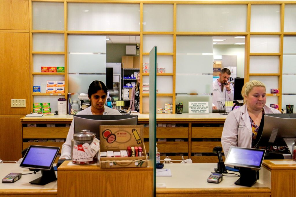 Pharmacy Technicians Vijaya Modugula, left, of Hanover, N.H., Jessica Prentice, of Lebanon, N.H., and pharmacist Michael Nardone, back, of Manchester, N.H., work in the outpatient pharmacy of Dartmouth-Hitchcock Medical Center in Lebanon, N.H., on Tuesday, Oct. 9, 2018. Modugula recently began her apprenticeship in the DHMC's Workforce Readiness Institute program after completing a nine-week training. She plans to continue as a pharmacy technician after completing the apprenticeship. (Valley News - August Frank) Copyright Valley News. May not be reprinted or used online without permission. Send requests to permission@vnews.com.