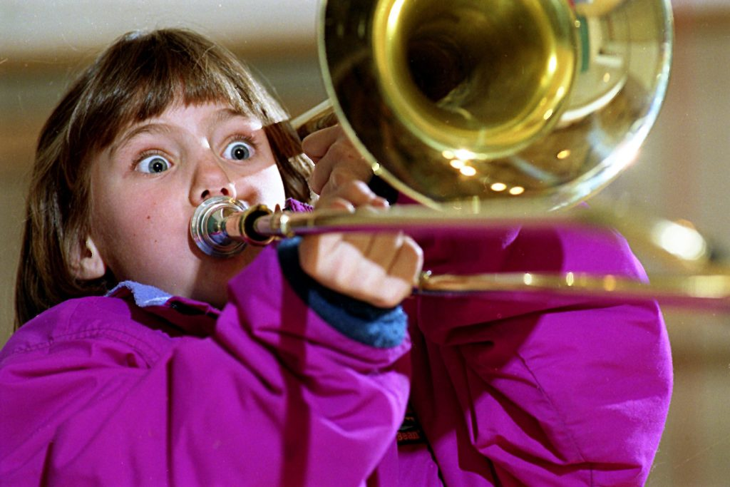 Fourth-grader Kathryn Harris, 9, tries out a trombone during a demonstration of band instruments by David Ellis of Ellis Music Co. at Marion Cross Elementary School in Norwich, Vt., on March 4, 1994. Ellis is carrying on a tradition started by his father, Richard Ellis, more than 45 years ago. (Valley News - Geoff Hansen) Copyright Valley News. May not be reprinted or used online without permission. Send requests to permission@vnews.com.