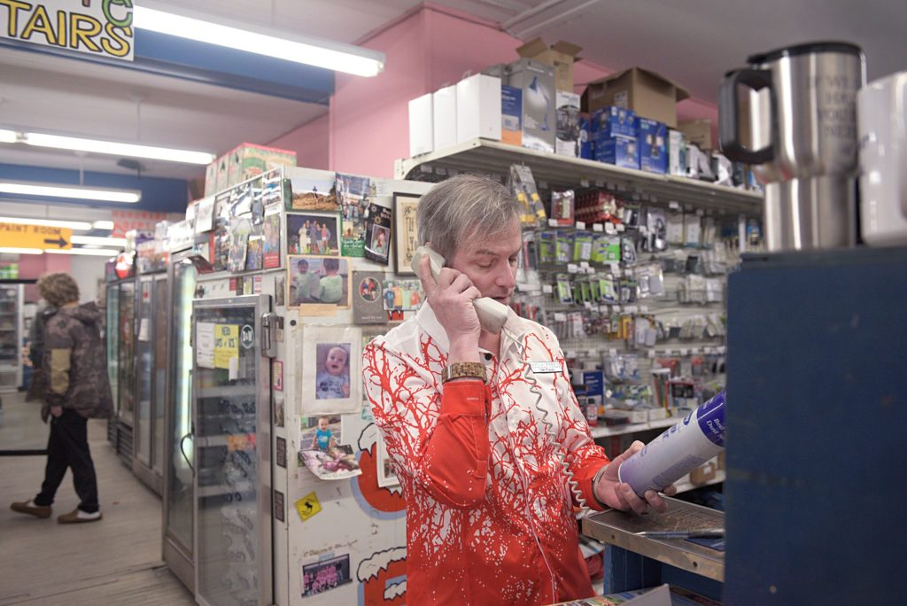 Dan Fraser, co-owner of Dan & Whit's General Store, checks a product for a customer in Norwich, Vt., on Jan. 7, 2019. Fraser is the third-generation family member to run the local store. (Valley News - Joseph Ressler) Copyright Valley News. May not be reprinted or used online without permission. Send requests to permission@vnews.com.