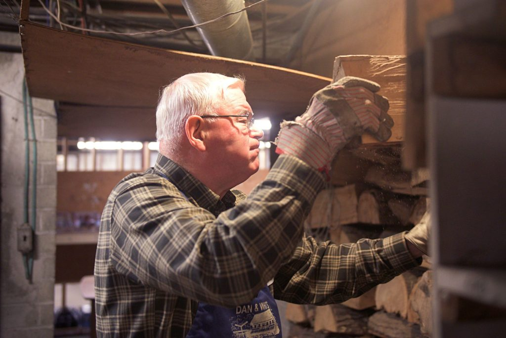 George Fraser, co-owner of Dan & Whit's General Store, grabs fuel for the woodstove in the store's basement in Norwich, Vt., on Jan. 7, 2019. Fraser is the eldest generation of this multigenerational area family business. (Valley News - Joseph Ressler) Copyright Valley News. May not be reprinted or used online without permission. Send requests to permission@vnews.com.