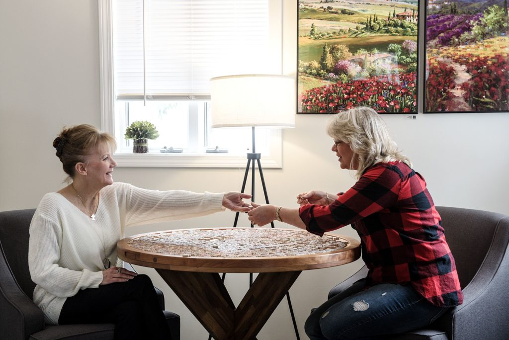 Jennifer Lennox, right, and Paula Tardie, left, have both worked for Stave Puzzles for 30 years and they bought the high-end jigsaw puzzle manufacturer from founder Steve Richardson in 2016. When sitting for a portrait at the company's Wilder, Vt., headquarters, the business partners turned their attention to a 1,000 piece puzzle laid out for visitors on Tuesday, Jan. 15, 2019. (Valley News - James M. Patterson) Copyright Valley News. May not be reprinted or used online without permission. Send requests to permission@vnews.com.