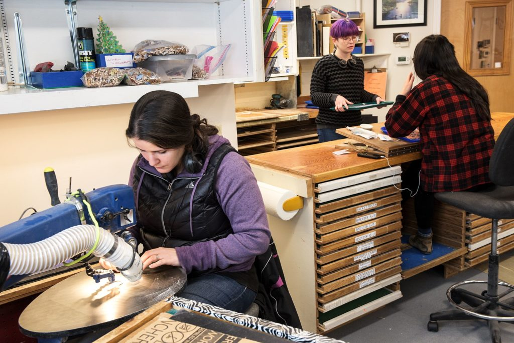 Christina Julian cuts a puzzle at left as apprentice employees Marisa Chapin, middle, and Kat Chau, right, work in the finishing area at Stave Puzzles, where pieces are touched up and the backs of the puzzles are sanded, polyurethaned and buffed in Wilder, Vt., Tuesday, Jan. 15, 2019. Apprentices work for six months to a year to learn the craft before their work can be sold. (Valley News - James M. Patterson) Copyright Valley News. May not be reprinted or used online without permission. Send requests to permission@vnews.com.