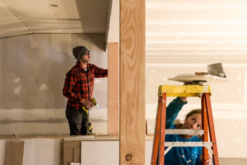 Peter Varkonyi, left, and his fiancee Lauren Stevens, of Brownsville, hang and mud drywall at the former Brownsville General Store in preparation for opening their new business, the Brownsville Butcher & Pantry, Monday, Sept. 24, 2018. They took the building down to its frame and have been pitching in to help contractors rebuild in preparation for creating a community gathering place that offers a cafe, meat, produce and toiletries. They hope to open on Oct. 20. (Valley News - James M. Patterson) Copyright Valley News. May not be reprinted or used online without permission. Send requests to permission@vnews.com.